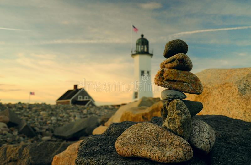 Cairns and lighthouse. Classic lighthouse in New England as a background royalty free stock images