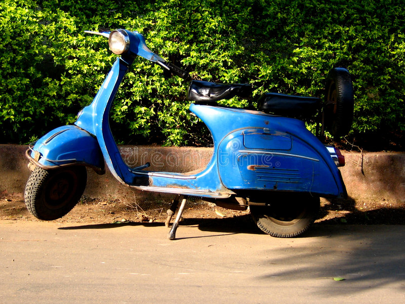 Old Scooter. An old blue Indian scooter against a wall of green creepers in bright sunlight royalty free stock image