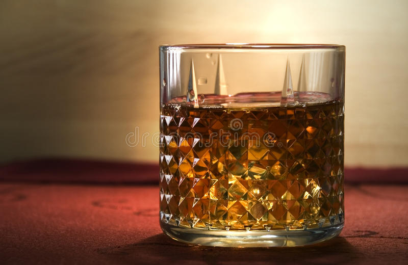 Old Scotch Whiskey. A glass of old whisky on the rocks royalty free stock photography