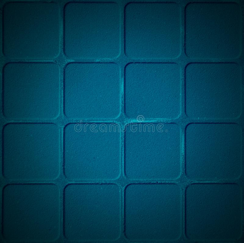 Old scratched and chapped painted dark blue wall with blocks stock photo