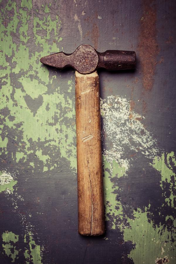 Old and scratched hammer on metal surface. Top view stock photo