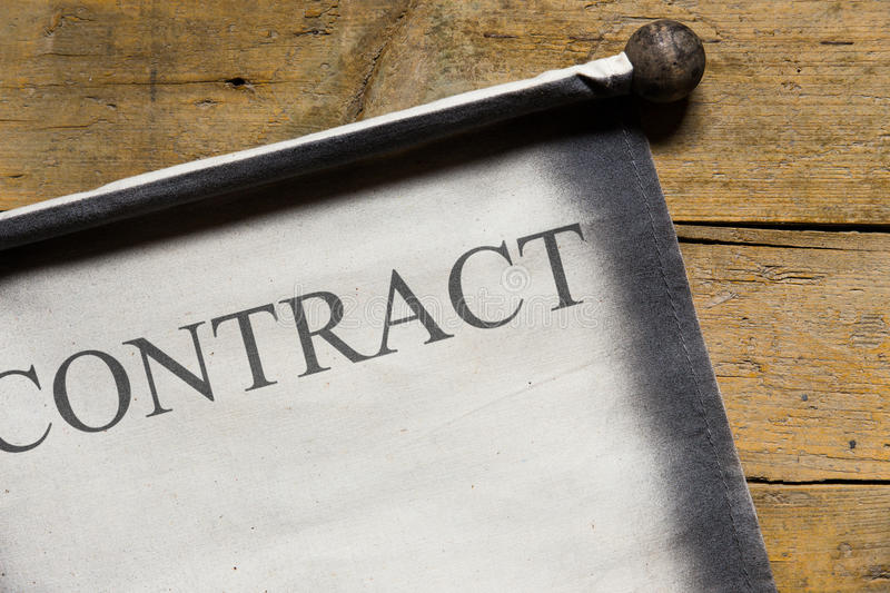 Old scroll on wooden table, word contract. Written on the document stock image
