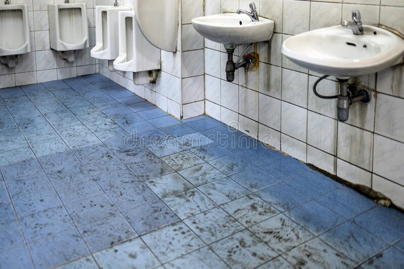 Old scruffy toilet where the floor is wet and filled with dirty footprints of student,filthy of urinals,washbasin,tiled wall, royalty free stock photos