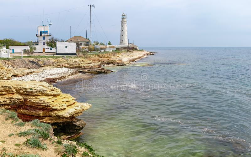 Old sea lighthouse on a low rocky limestone cape. Old sea lighthouse and other buildings on a low-level rocky cape against sea and sky stock image