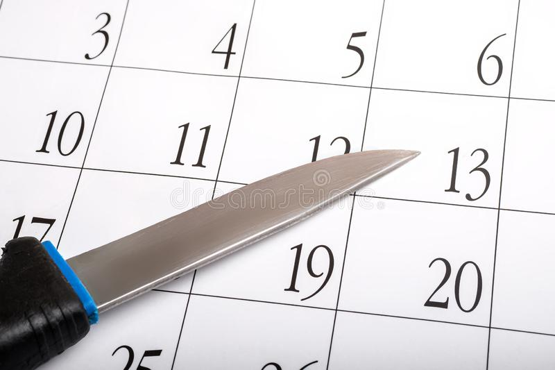 An old secondhand knife on a calendar sheet with dates. Plan a murder with a knife stock photos