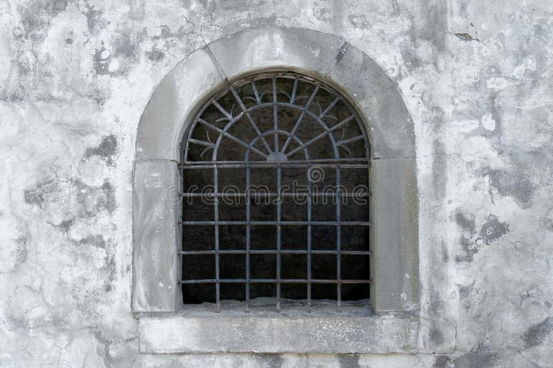 Semicircular lattice window in an old facade. Old semicircular open lattice window in the gray facade of a medieval building stock photo