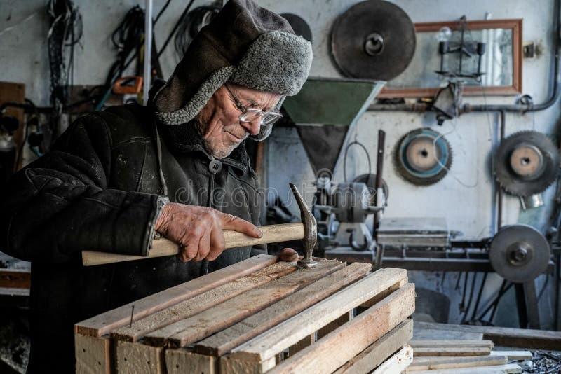 Old senior carpenter in grey warm clothes in eyeglasses stock image