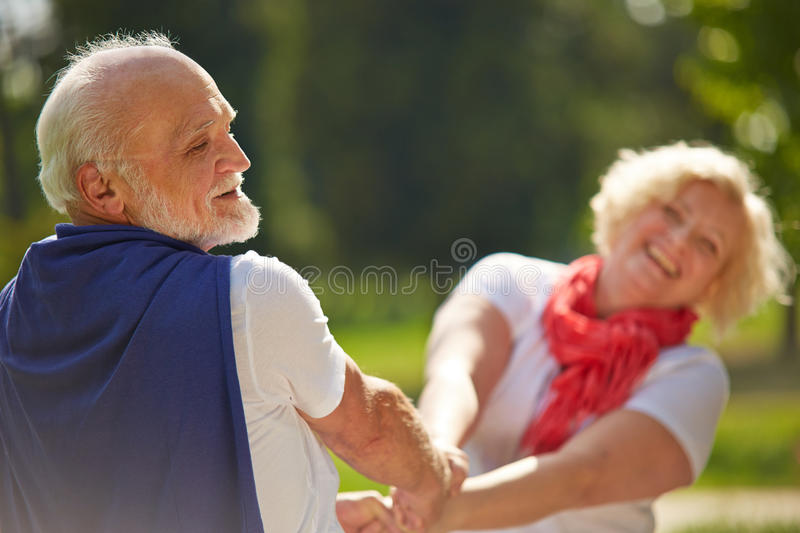 Old senior couple dancing in nature royalty free stock photography