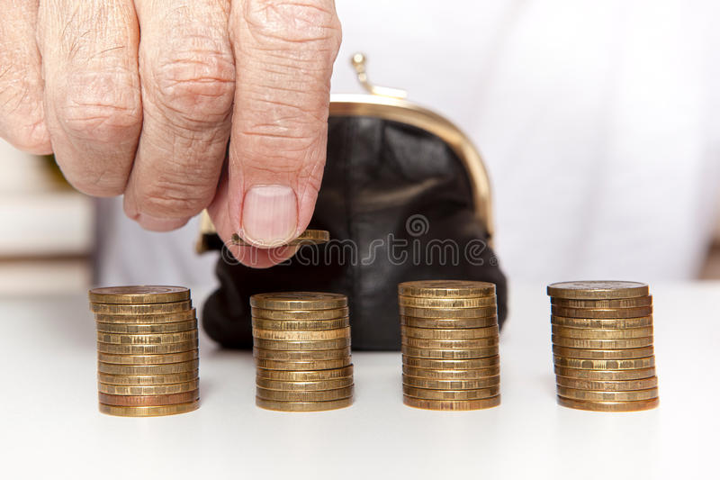Old senior hands holding coin and small money pouch stock images