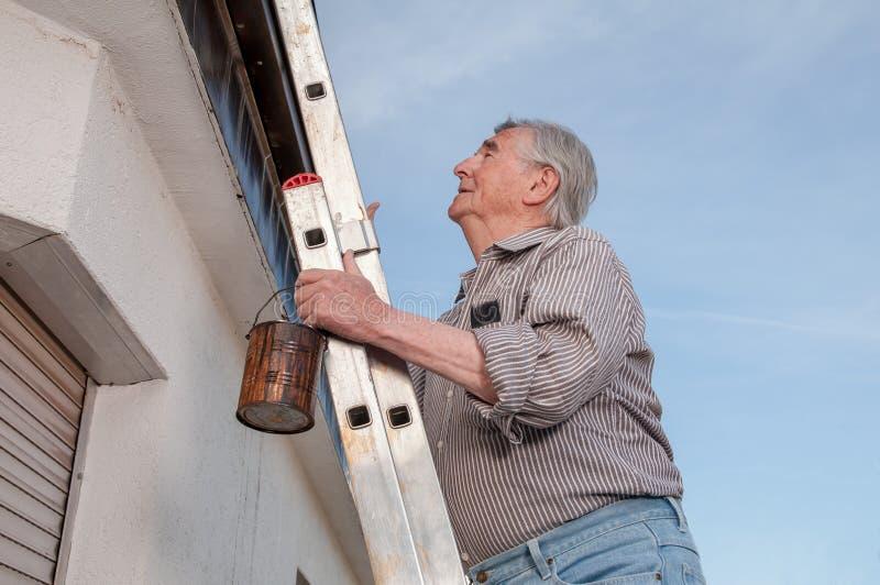 Senior man climbing up a dangerous ladder royalty free stock photos