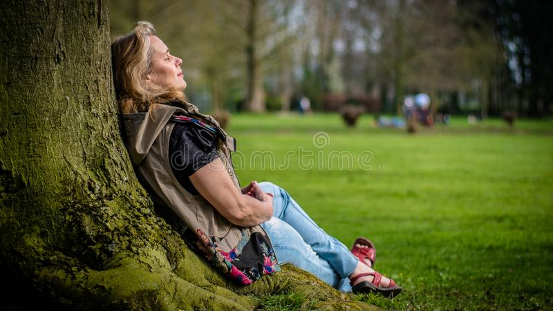 Old senior woman is relaxing at a tree in a public park during day royalty free stock photos