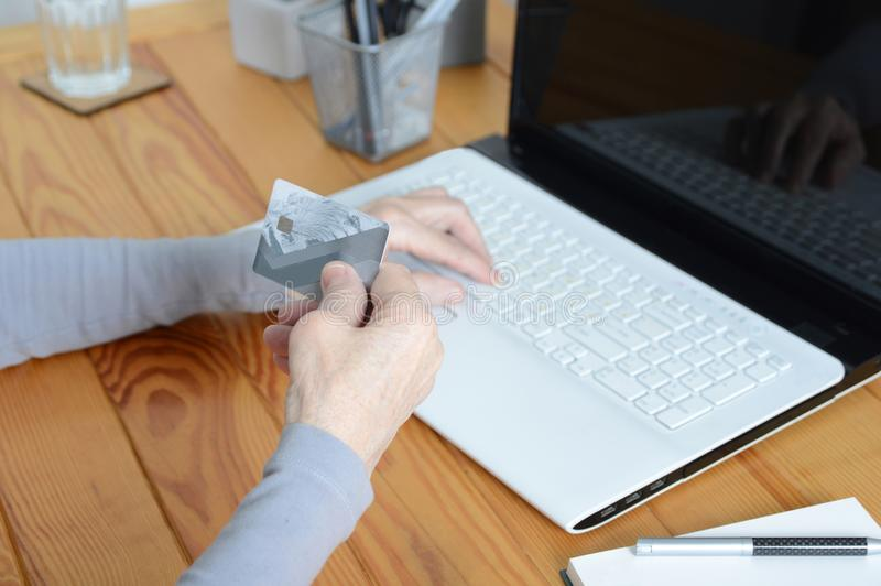 Old senior woman using laptop and holding credit card royalty free stock images