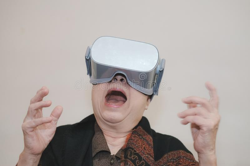 Old senior woman wearing virtual reality goggles. VR headset device. Old asian senior woman wearing virtual reality goggles. VR headset device royalty free stock photography