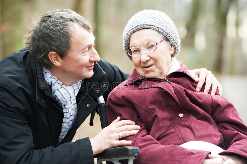 Old senior woman in wheelchair with careful son stock photo
