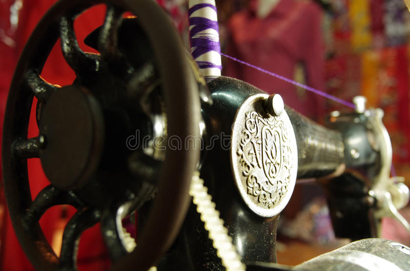 Old sewing machine, black with silver emblem. Antique sewing machine, black with silver emblem, purple thread on top royalty free stock image