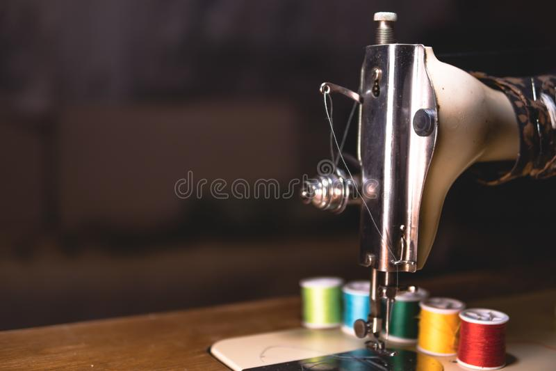 Old sewing machine with colour thread, on a old grungy work table. Tailor`s work table. textile or fine cloth making. industrial stock images
