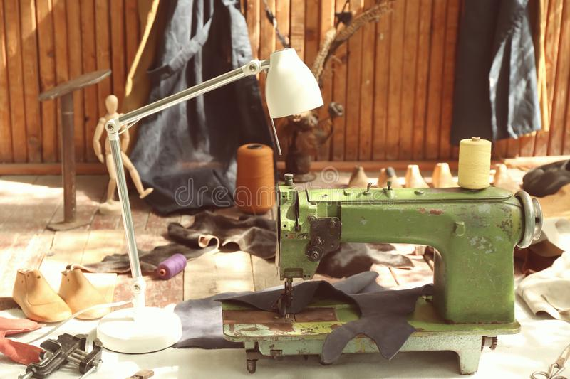 Old sewing machine with leather and craft items on floor in workshop stock photo