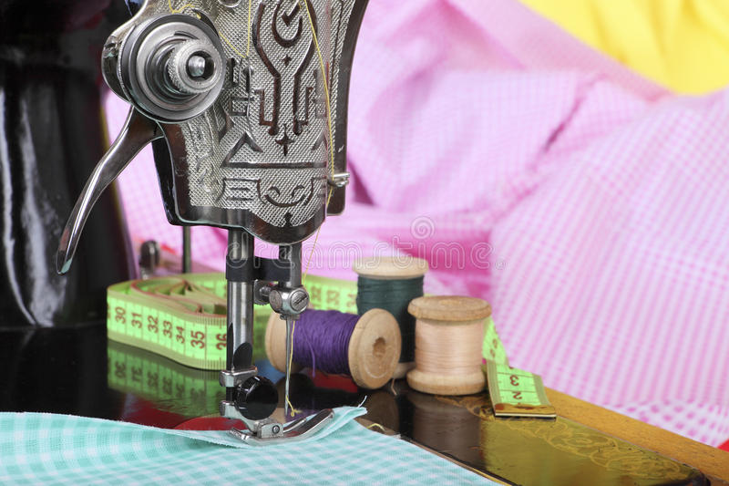 On the old sewing machine lie wooden retro coils with threads, a thimble, a measuring tape and a piece of cotton fabric. Close-up. Retro stylized photo stock image