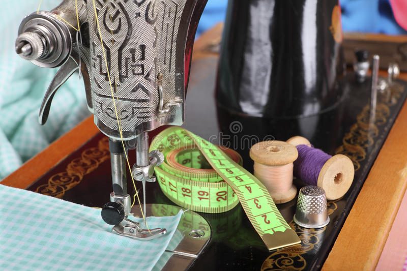 On the old sewing machine lie wooden retro coils with threads; a thimble, a measuring tape and a piece of cotton fabric. Focus on. The needle and thread. Retro royalty free stock photos