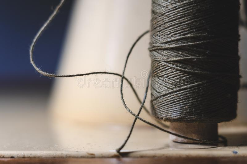 Old sewing machine needle with black thread, on a old grungy work table. Tailor`s work table. textile or fine cloth making. indust stock image