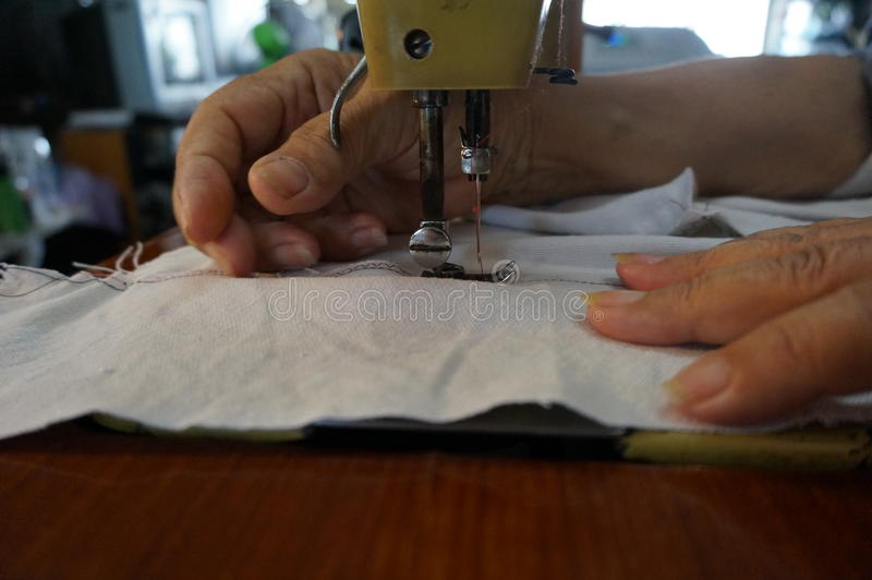 Old sewing machine is sewing cloth with woman`s hands royalty free stock photography