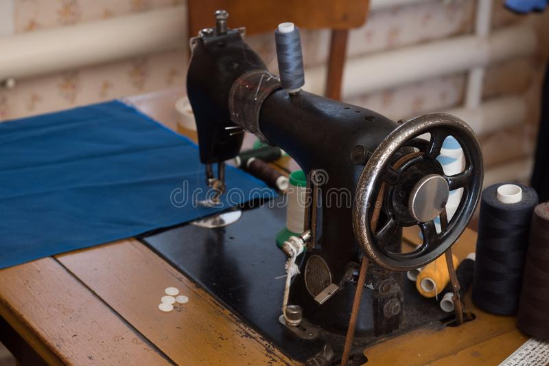 the old sewing machine is sewn blue cloth in the home workshop stock