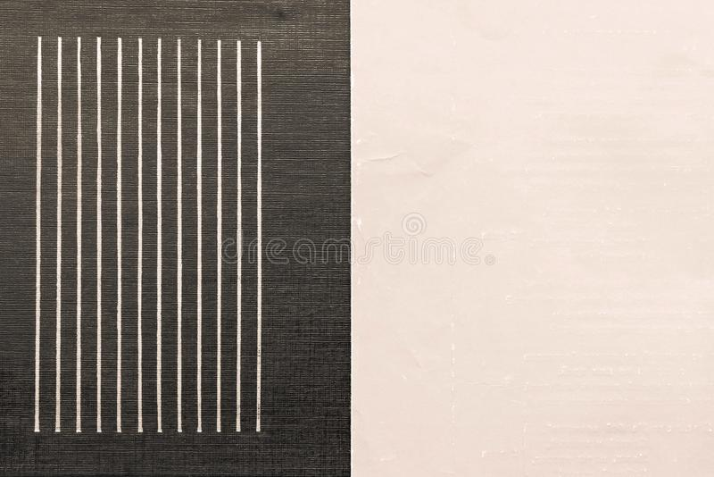 Old shabby beige paper and corrugated black leather. The combined textured corrugated black leather material with strips and the old shabby beige paper for stock images