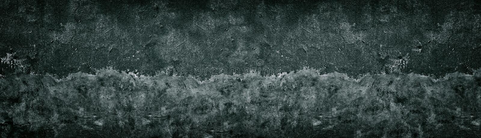Old shabby black half painted concrete wall texture. Wide dark grunge background stock photos