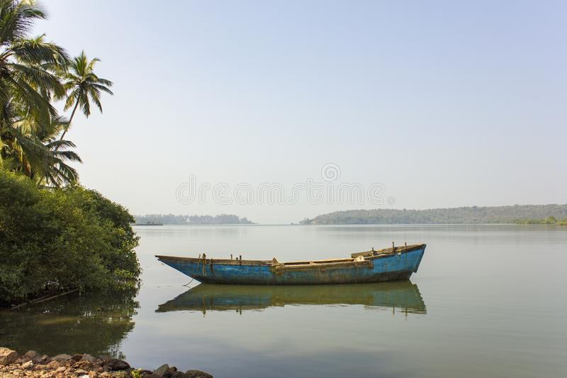 Old shabby blue boat on the water near the green palm trees on the background of the river misty valley royalty free stock image