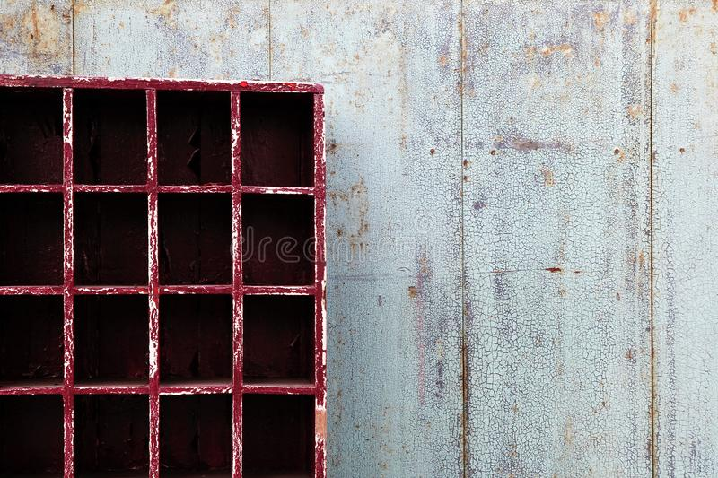 Old shabby blue wooden wall with empty red cupboard. royalty free stock photo