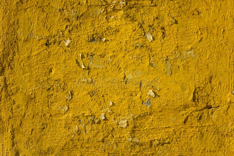 Old shabby bright yellow wall with deep relief, scraps of paper and cracks with shadows. rough surface texture. An old shabby bright yellow wall with deep relief stock photos