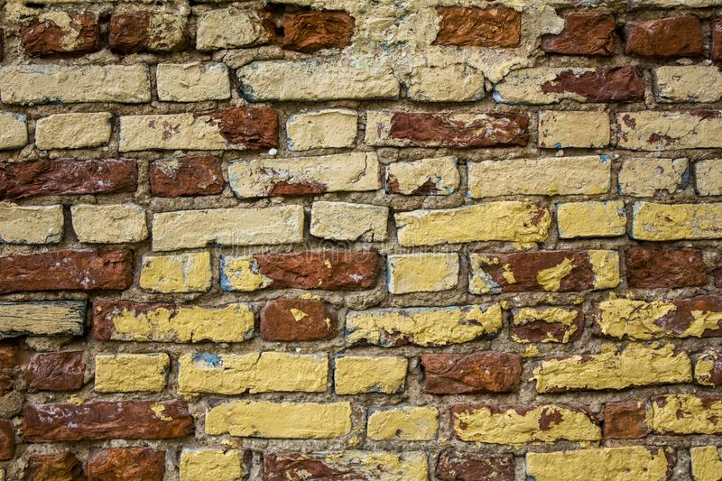 Old shabby damaged white, beige, red brick wall with yellow spots of paint closeup. rough surface texture. A old shabby damaged white, beige, red brick wall with stock photography