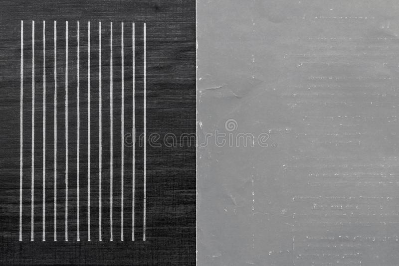 Old shabby gray paper and corrugated black leather. The combined textured corrugated black leather material with strips and the old shabby gray paper for stock photo