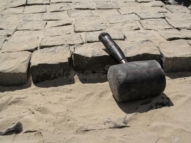 An old shabby huge mallet lies at the workplace of the unfinished paving stones. Beautiful building background - the concept of laying paving slabs and granite royalty free stock image