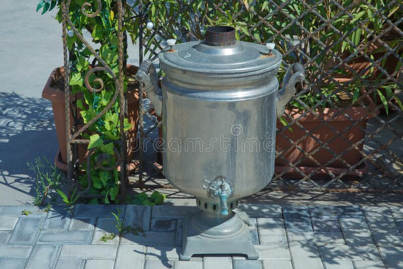 Old shabby iron samovar .Vintage metal copper tea . Samovar side view. Retro soot grunge tea samovar was used for a long time. stock images