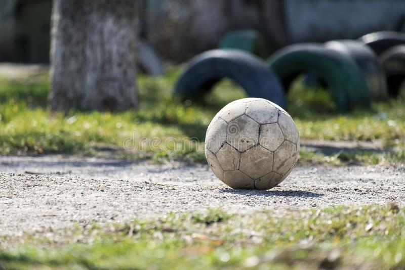 Old shabby leather soccer ball lying on the ground. Shabby leather soccer ball lying on the ground stock photography