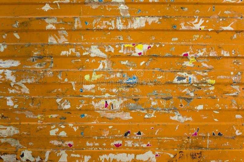 Old shabby orange metal wall with colored scraps of paper ads of different shapes and sizes. horizontal lines. rough surface. A old shabby orange metal wall with stock images