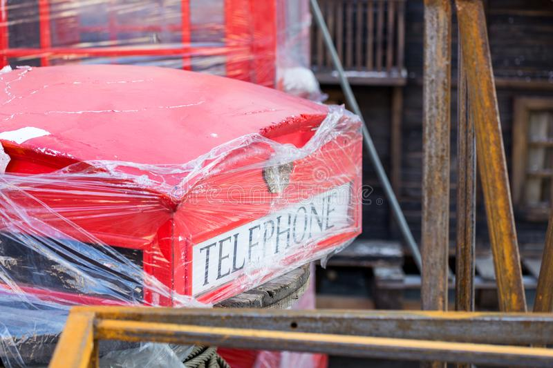 Old shabby replica of London Red telephone box. Rusty metal structures, old broken decoration of movie scenery on backyard stock photos