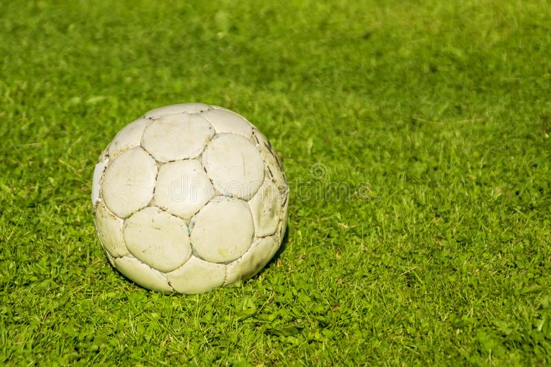 Old shabby soccer ball on a green lawn stock photos