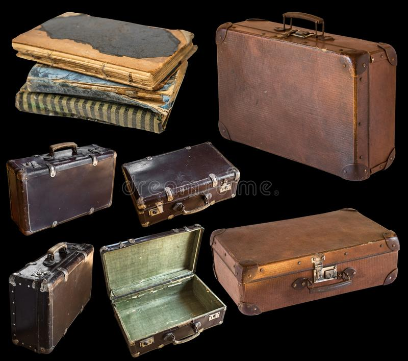 Old shabby vintage suitcases and book isolated on black background. Retro style royalty free stock images