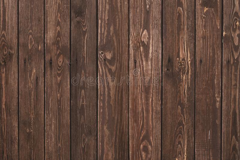 Old shabby wooden fence. Abstract pattern texture background. Brown faded boards. Oak bars, logs. Wood surface. Vertical stripes t royalty free stock photography
