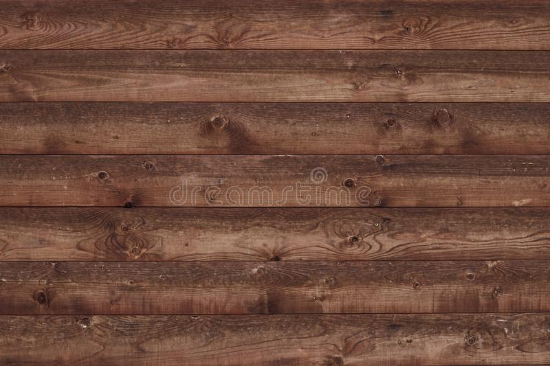 Old shabby wooden fence. Brown faded boards. Oak table, bars, logs. Wood surface. Abstract pattern texture background. Strips, str. Ipes brown slats. Parallel royalty free stock photos