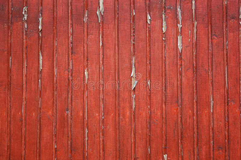 Old shabby wooden planks with red cracked color paint as a background. Texture of old painted boards. royalty free stock photography