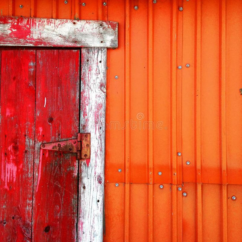 Old shack with red door and orange wall. Old shack with red door in wood and orange metallic wall with apparent nuts stock photo