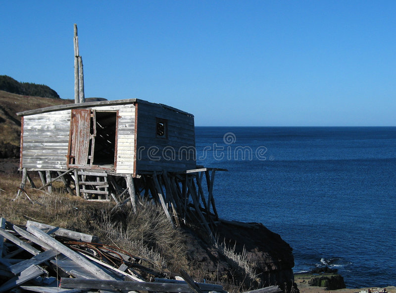 Old Shack by the Sea. An old, abandoned shack teetering on the edge of a cliff overlooking the ocean stock photos