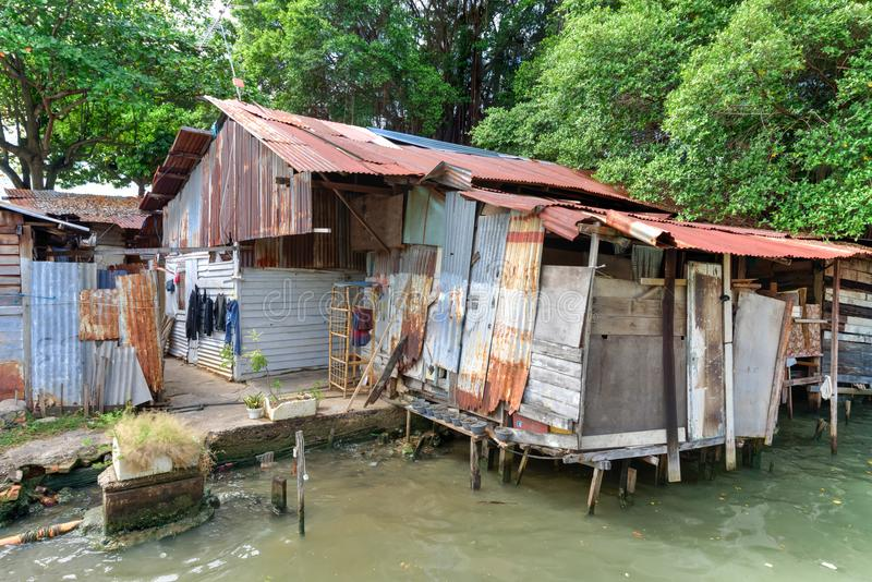 Old shack slum house near Malacca river. Close-up old shack slum house near Malacca river. Old wooden hut on stiltson the bank of river in Melaka royalty free stock photos