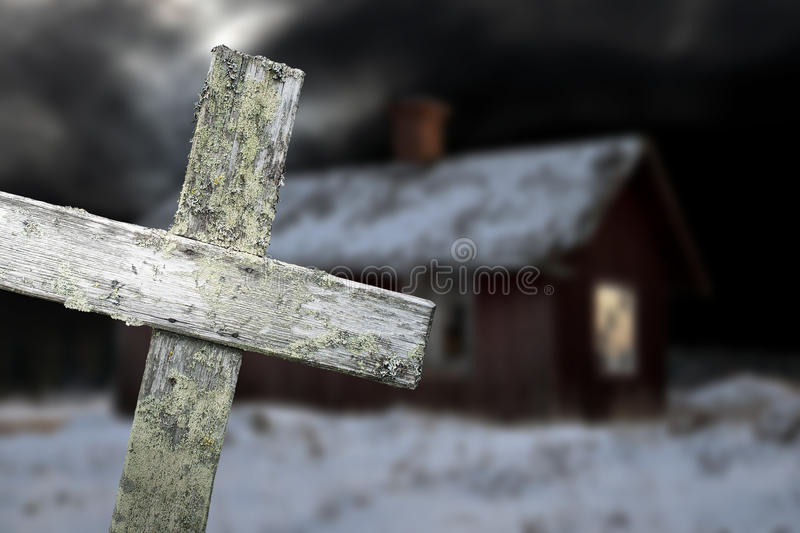 Old shack and wooden cross. Old shack in winter evening with wooden cross in foreground royalty free stock photo