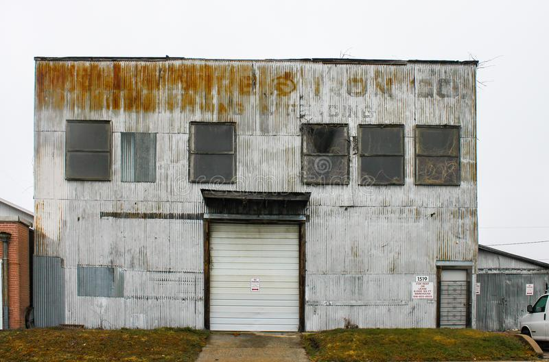 Old sheet metal industrial building with faded lettering and plants growing in windows and out of roof and for rent sign Tulsa OK royalty free stock photos