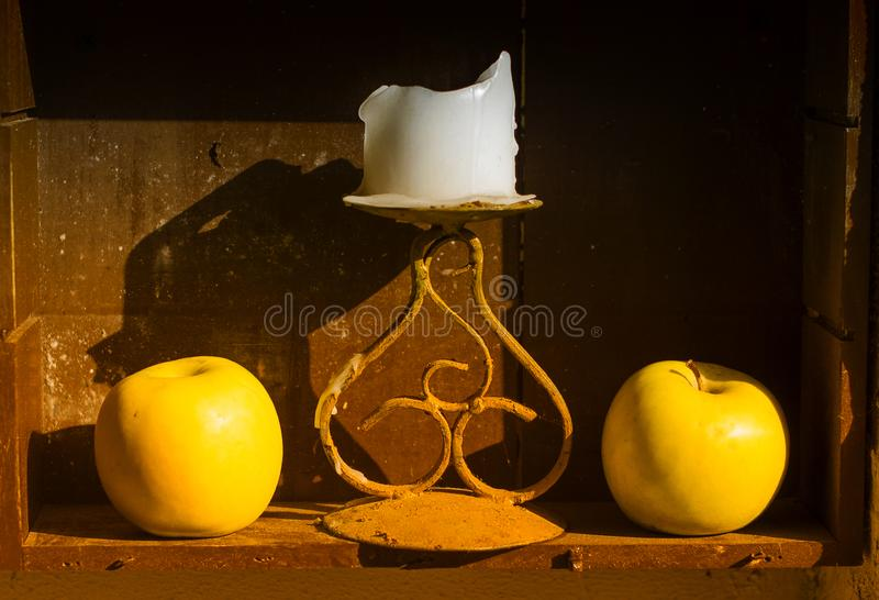 Two yellow apples and candle stock image