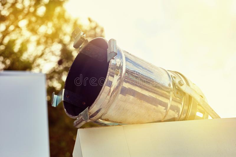 Old broken searchlight on a background of wood and sky royalty free stock photography